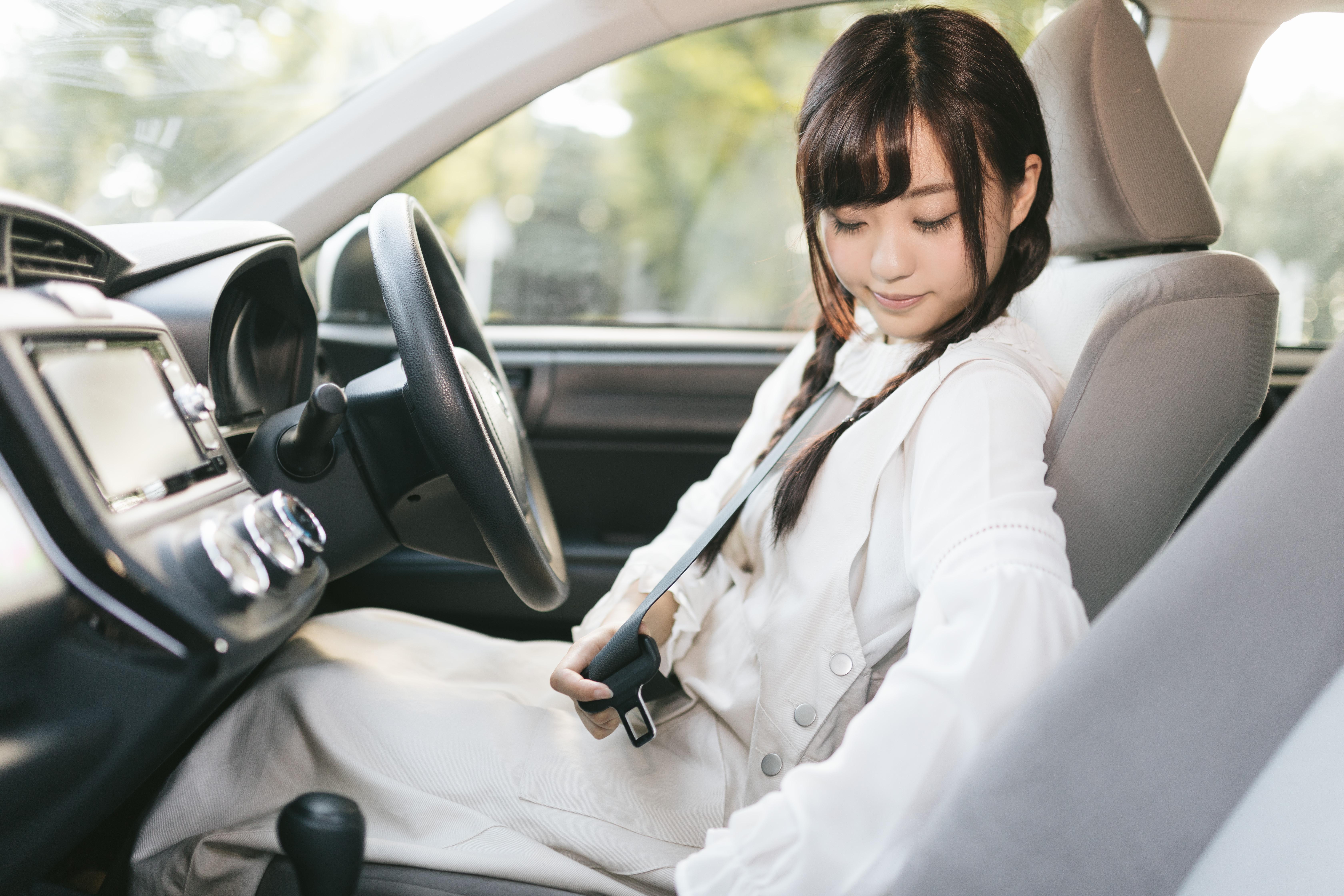 良い中古車を見つけ試乗する女子
